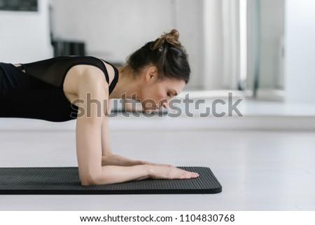 Pretty Caucasian woman doing pilates exercise on mat. #1104830768