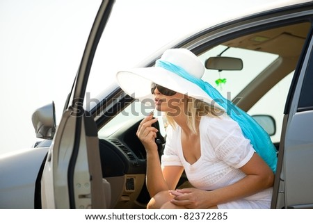 Pretty caucasian woman putting lipstick on using the car mirror