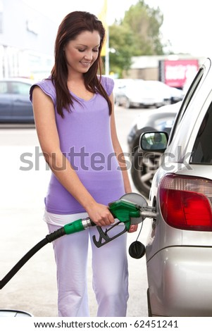 Pretty caucasian woman refueling her car in a service station