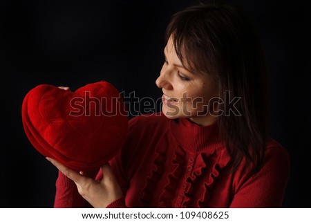Pretty Caucasian woman with a happy heart pillow on a dark background