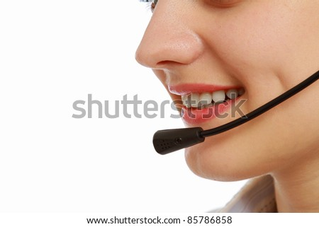 Pretty caucasian woman with headset smiling during a telephone conversation. Part of face isolated on white background