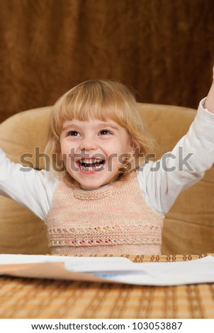 Pretty Caucasian young baby draws a table on a brown background