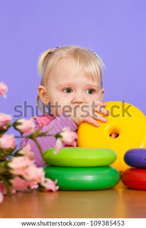 Pretty Caucasian young girl sitting at a table on a violet background