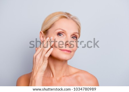 Pretty, charming, attractive woman touching, enjoying her perfect face skin, holding fingers on cheek, pimple, whelk, pustule, dry, oiled, problem skin concept, isolated on grey background