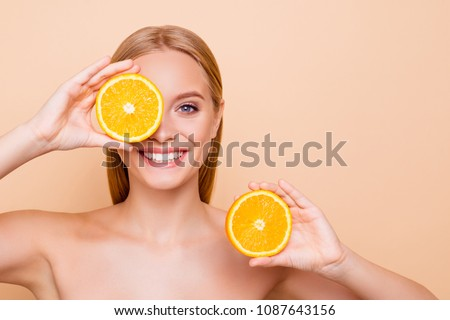 Pretty charming joyful attractive cheerful funny comic positive nude natural pure girl having two pieces of orange, closing one eye, isolated on beige background with copy space for advertisement
