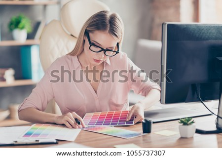 Pretty, charming, stylish woman working with colour chart, sitting at desk on armchair in workstation, choosing suitable color for her sketch
