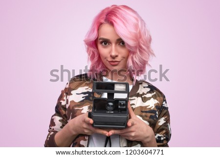 Pretty charming woman with pink hairstyle wearing camouflage jacket and holding vintage photo camera on pink background
