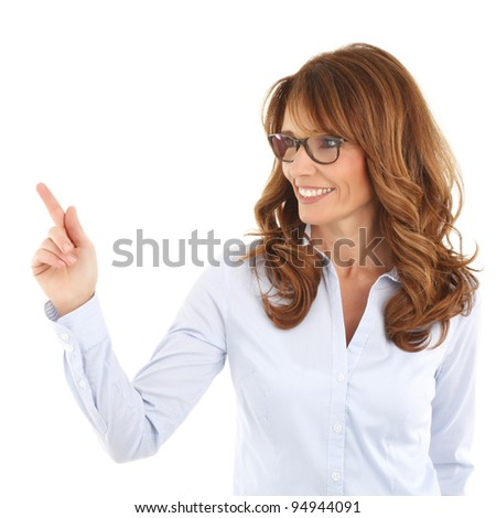 Pretty cheerful business woman pointing at something in the air with her index finger. White background
