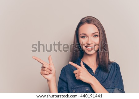 Shutterstock Pretty cheerful woman gesturing with fingers and showing away