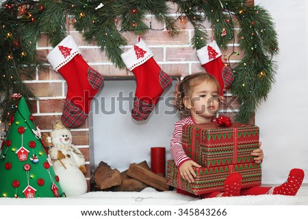 Pretty child girl holding some packed gifts near Christmas decorated fireplace, winter holiday family concept