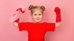 Pretty child in red t-shirt and red gum gloves showing strength gesture. Little happy smiling girl on pink background ready for cleaning.