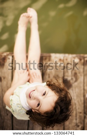 pretty child sitting on wooden...