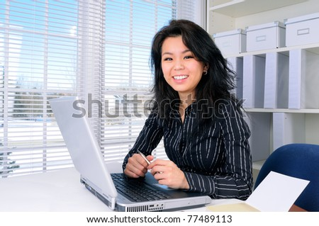 Pretty Chinese Business Woman With long Hair Sat At Her Office Desk