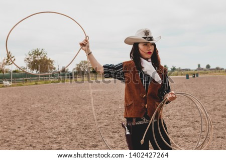 pretty Chinese cowgirl throwing the lasso in a horse paddock on a wild west farm