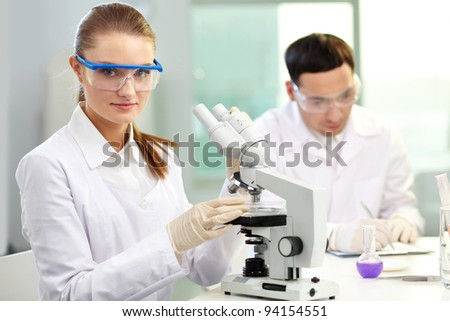 Pretty clinician with microscope looking at camera in laboratory