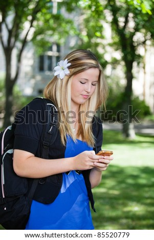 Pretty college girl busy texting on cell