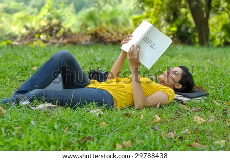 Pretty college girl lays on grass while reading a book