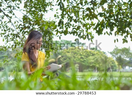 Pretty college girl sits on grass while reading a book