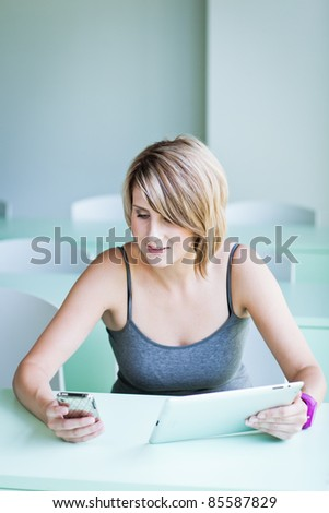 Pretty college student/businesswoman using her cell phone and a tablet computer (shallow DOF; color toned image)