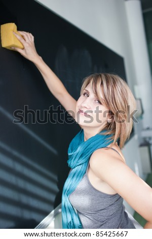 pretty college student erasing the chalkboard/blackboard during a math class (color toned image; shallow DOF)