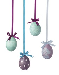Pretty Colored Easter Eggs hanging on Ribbons with bows isolated on white