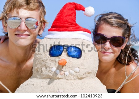 Pretty couple having fun at beach with perfectly build christmas snowman made out of sand wearing sunglasses