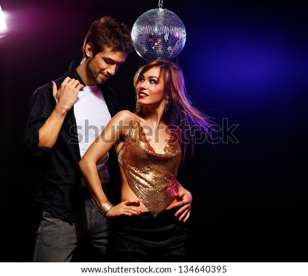 Pretty couple of young people dancing on a disco