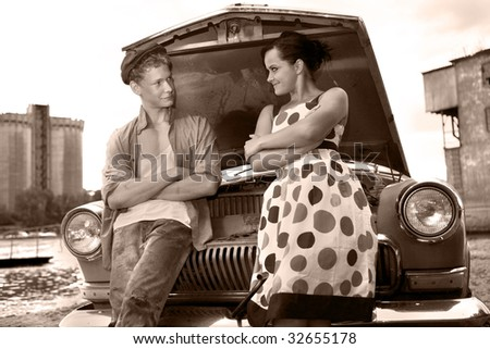 Pretty couple on the broken car background.
