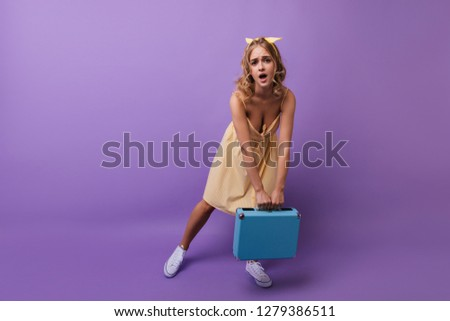 Pretty curly girl posing with heavy suitcase. Debonair european woman holding her valise on violet background.