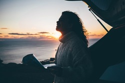 Pretty curly haired woman in white sweater reads map sitting on open trunk of contemporary automobile on ocean cliff beach at bright sunset light