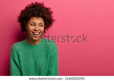 Pretty curly haired woman looks aside with dreamy happy expression, smiles broadly, expresses good emotions, wears green sweater, has appealing appearance, isolated on pink wall with empty space