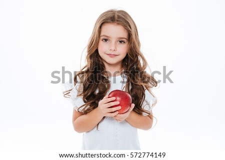 Pretty curly little girl standing and holding red apple over white background #572774149