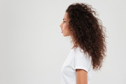 Pretty curly woman posing in profile over gray background