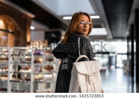 Pretty cute young woman with smile in a fashionable jacket with hood in stylish glasses with a stylish vintage backpack is walks on a shopping center. Urban girl fashion model on the vacation. Fashion