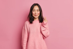 Pretty dark haired woman with gentle smile makes korean like sign expresses love to you wears casual long sleeved jumper isolated over pink background. Mini heart gesture. Body language concept