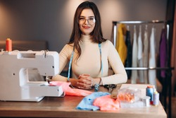 Pretty dressmaker woman in glasses sews clothes on sewing machine. Smiling seamstress in workshop. Creating online clothing design courses.