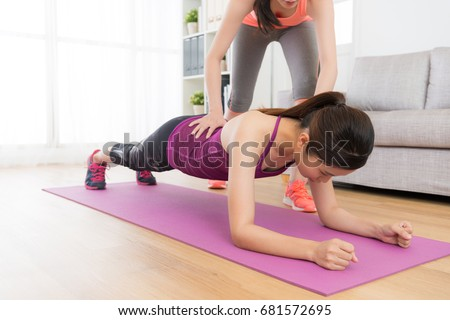 pretty elegant fitness woman doing workout class at home with personal trainer and making planking to workout body muscle.