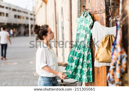 Pretty elegant woman shopping in the vintage clothes store outside in old historical center in Jaffo in Israel. Moment of vocation or holiday.
