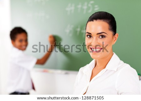 pretty elementary school teacher and student in front of chalkboard