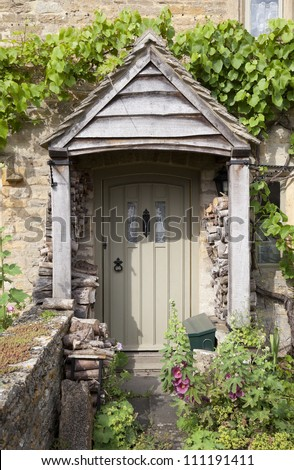 Pretty English cottage doorway with logs and flowers