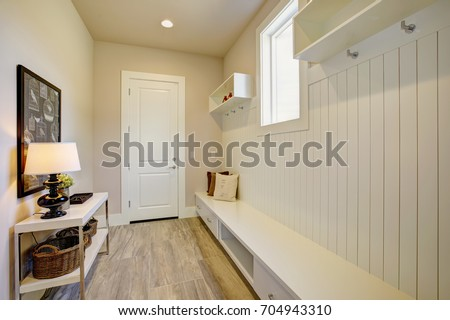 Pretty entrance foyer with a wall clad in board and batten lined with an extra long built-in bench with storage drawers facing white console table with three round wicker baskets. Northwest, USA