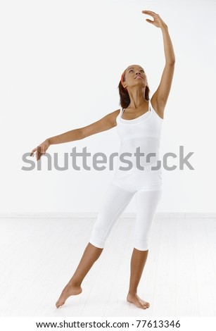 Pretty ethnic classical dancer in ballet posture, looking up.?