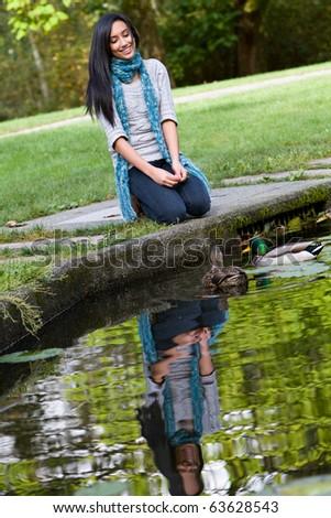 Pretty ethnic girl feeding ducks