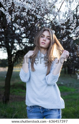 Pretty euroepan  model touches her hair and posing on camera. Young woman stands in park on blossom trees background. Dressed in white sweater and blue jeans. She looking at camera. Medium long shot.