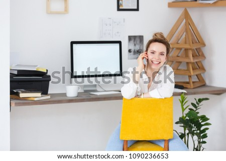 Pretty European blonde female uses modern cell phone, chatts with friends, sits at working place. Work of creative designer in the office with digital devices #1090236653
