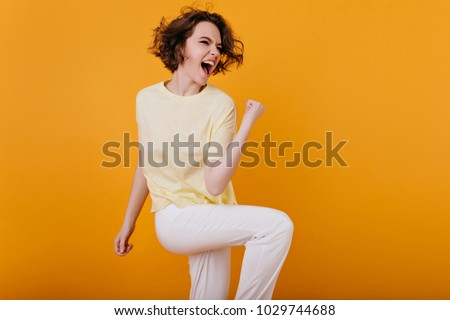 Pretty excited european woman funny dancing in studio with orange interior. Indoor photo of enthusiastic curly girl in white atiire spending time at home.