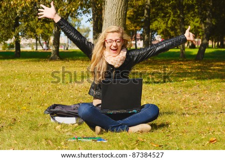 pretty excited girl with a laptop in the park