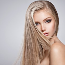 Pretty  face of young woman with long white hair - posing at studio over gray background