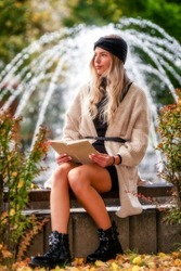 Pretty face young blonde girl with hat posing with book in park with fountain