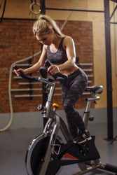 pretty fair haired sportswoman is working out with enthusiasm in the stationary bicycle in the gym with modern interior. side view photo